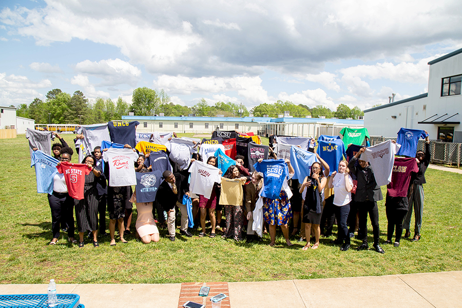 <p>Students at KIPP Gaston hold up T-shirts of colleges they were admitted to on College Signing Day. (Richard Whitmire/The 74)</p>